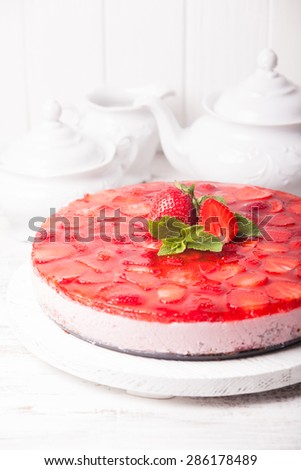 Strawberry cake on white wooden plate with mint leaf - stock photo
