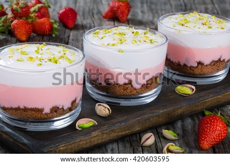 Strawberry Cheesecake Mousse Cups decorated by egg white cream frosting and chopped pistachios, close-up - stock photo