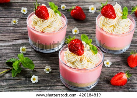 Strawberry Cheesecake Mousse Cups decorated by homemade ice cream, mint leaves and strawberry flowers on an old rustic wooden table, studio lights, top view, close-up - stock photo