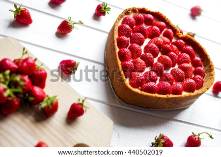 strawberry cheesecake on white table with berries - stock photo