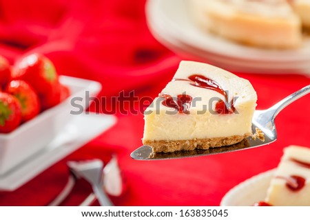 Strawberry Cheesecake slice sitting on cake knife with strawberries and red background. Horizontal composition. - stock photo