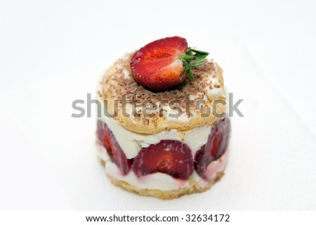 Strawberry cheesecake with mascarpone cream decorated with chocolate chips and a half a strawberry - stock photo