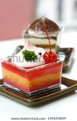 strawberry cheesecake with red cherry on top on wood table, bakery cake shop,  sweet and dessert. isolated