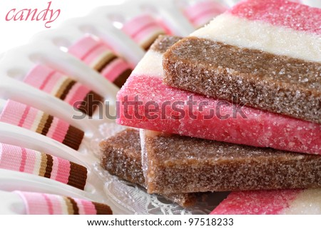 Strawberry, chocolate, and vanilla coconut candy on ceramic plate with color coordinated ribbon.  Macro with extremely shallow dof.  (Text is on solid white and easy to remove.) - stock photo