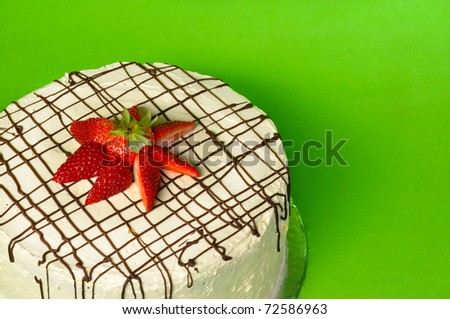 Strawberry chocolate cake on green background with copy space - stock photo
