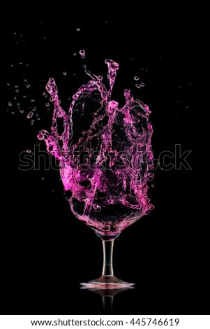 strawberry cocktail splash out of glass on black background.