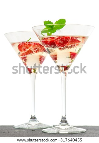 Strawberry cocktail with berries in martini glass isolated on white background. Festive arrangement with sparkling wine and fresh fruits