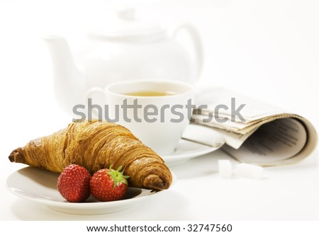 strawberry, croissant, teapot and white teacup with hot tea on white background - stock photo