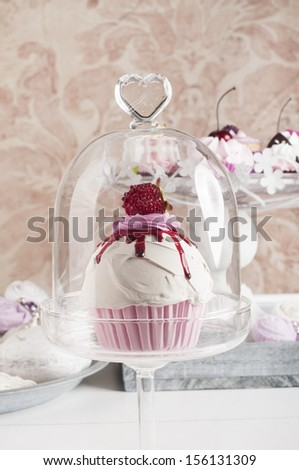 strawberry cupcake on a glass cupcake stand