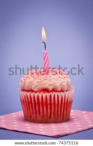 Strawberry cupcake with vanilla frosting and candle with blue background.