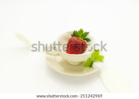 strawberry falling into ceramic cup with cream splashing isolated on white background