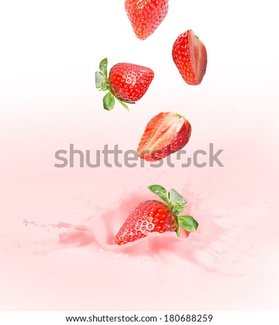 Strawberry falling into splashing milk or yogurt. - stock photo
