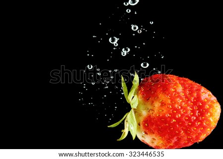 Strawberry falling into water at black background - stock photo