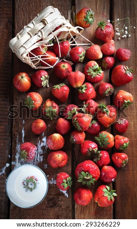 strawberry fell out of the basket and scattered on the possible next table with a glass with cream - stock photo