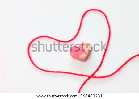 Strawberry flavored cookie in heart shape put in yarn design heart shape too, for in love.