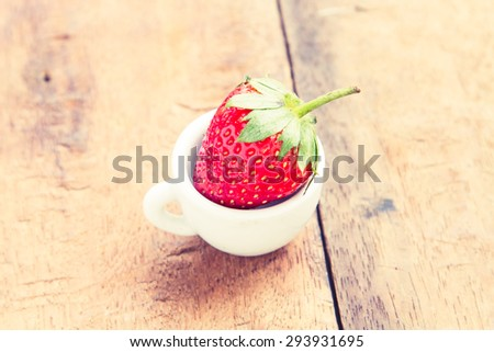 Strawberry fresh and tasty ingredients in a cup on a wooden table made of old and vintage. - stock photo