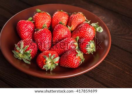 Strawberry, fresh strawberry, ripe strawberry, healthy strawberry, strawberry on the plate on wooden background - stock photo