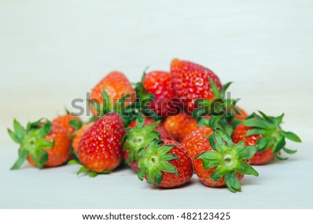 Strawberry fruit with flash filled on wooden board (Other names are Fragaria strawberry, Fragaria ananassa)