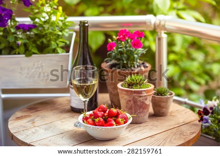 Strawberry, glass of wine and flowers on small wooden table on beautiful terrace or balcony - stock photo