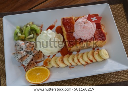 Strawberry honey Toast bread topped with ice cream, strawberry sevred with fruit and whipped cream,process color