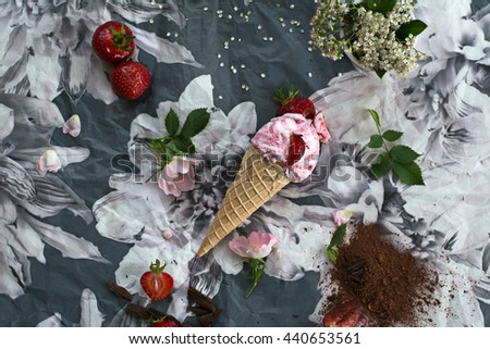 Strawberry ice cream in a waffle cone over black & white floral background. Fresh fruits, cocoa and dark chocolate. White and pink flowers.  - stock photo