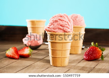 strawberry ice cream in waffle cones on wood with a scoop in background - stock photo
