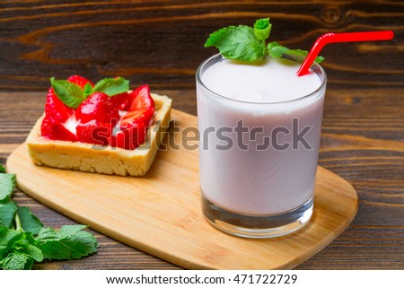 Strawberry ice cream with a cup of yogurt on a wooden background