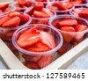 Strawberry in a plastic glass. - stock photo