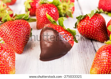 Strawberry in chocolate. Melted Chocolate pouring on fresh ripe juicy strawberry close up. Dessert. Gourmet food. Fondue - stock photo