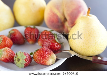 strawberry  in plate,spoon, pear and peach on a wooden table