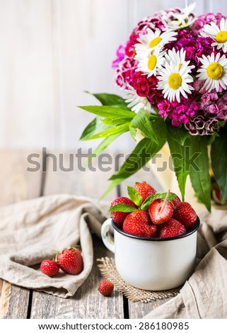Strawberry in the cup near flower bouquet on wooden table - stock photo