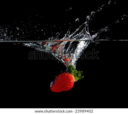 Strawberry in water with bubbles on black ground - stock photo