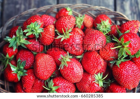 Strawberry in wicker plate on wooden background