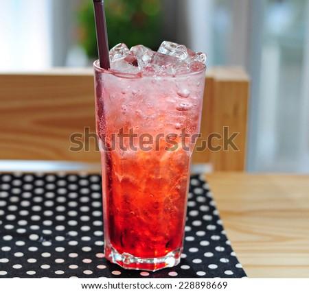 Strawberry italian soda on wood table with black polka dot tablecloth. - stock photo