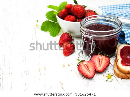 Strawberry jam and fresh strawberries on a wooden background - stock photo