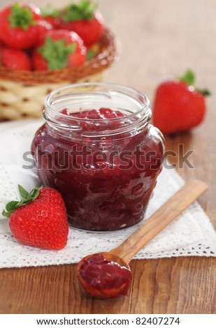 Strawberry jam and fresh strawberries on the wooden table - stock photo