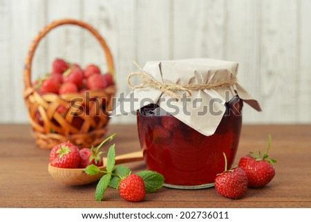 Strawberry jam in a jar with fresh berries on  the wooden background