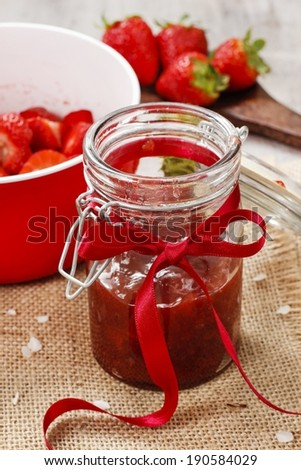 Strawberry jam in preserving glass - stock photo