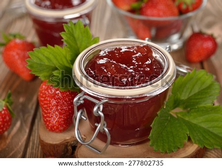 Strawberry jam on a brown background - stock photo