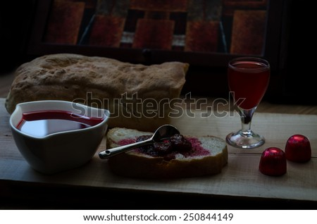 Strawberry jam (sweet) in a bowl on wooden table with slice of bread, glass of strawberry juice and strawberry candies in wrapper. Retro, vintage look - stock photo