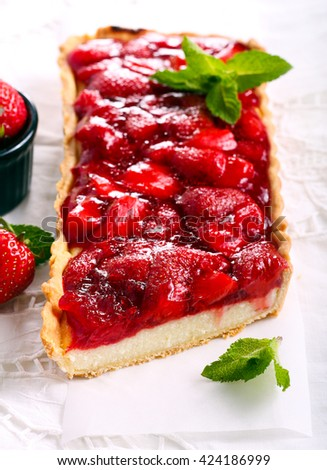 Strawberry jelly topping cheesecake tart, on table