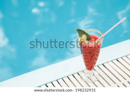 strawberry juice near swimming pool - stock photo