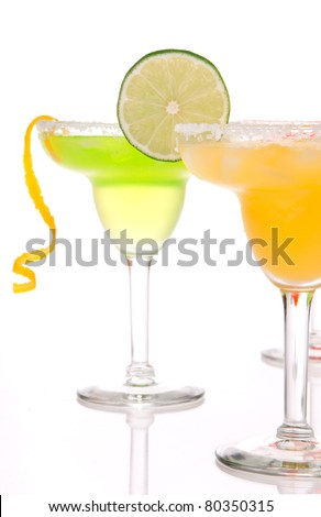 Strawberry, lime, apple Margaritas cocktails composition decorated with twisted lime, mint, cherry, cocktail umbrella in margarita glass isolated on a white background