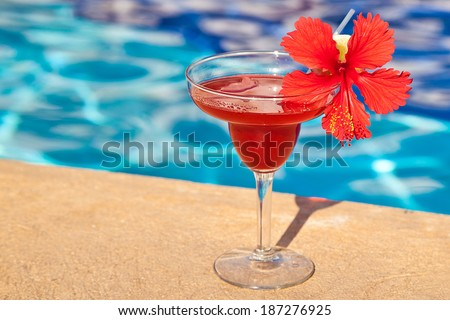 Strawberry margarita cocktail drink at the edge of the swimming pool. - stock photo
