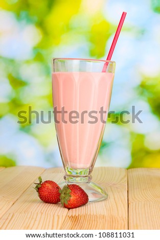 Strawberry milk shake on wooden table on bright background