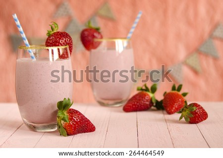 Strawberry milkshake in glasses and striped straws on pink boards and pink background.