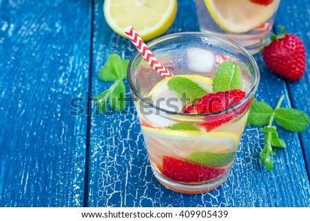 Strawberry mint homemade lemonade on blue wooden table - stock photo