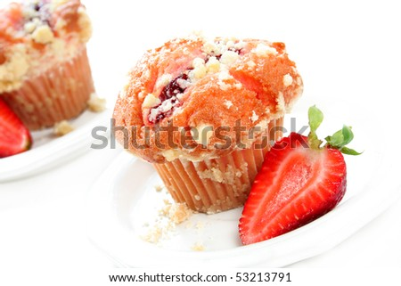 Strawberry muffin on a white plate with a fresh cut strawberry on the side. - stock photo