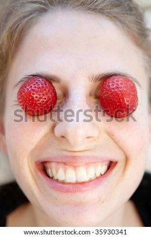 strawberry on the eyes of a young nordic style smiling woman (natural beauty) - stock photo