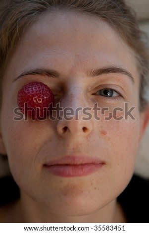 strawberry on the eyes of a young woman - stock photo